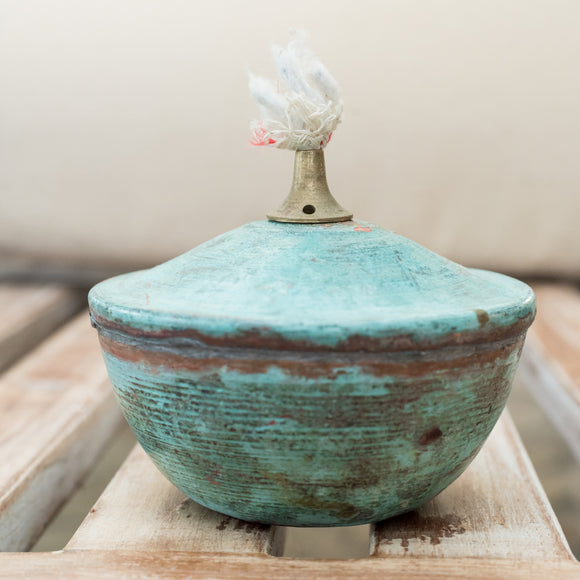 a green vase sitting on top of a wooden table