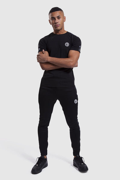 model wearing Firestone II top and gym joggers in black