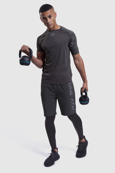 Man lifting kettlebells in training tops and shorts