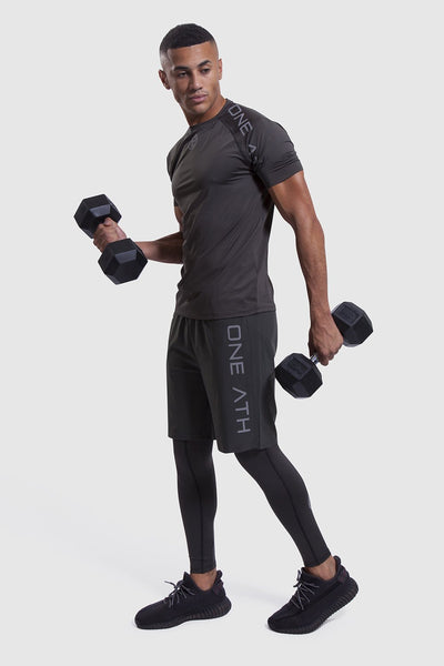Person lifting 2 dumbbells in mens gym t-shirt and shorts