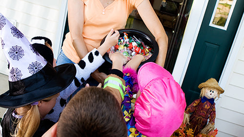 woman passing out candy to trick-or-treaters on front porch