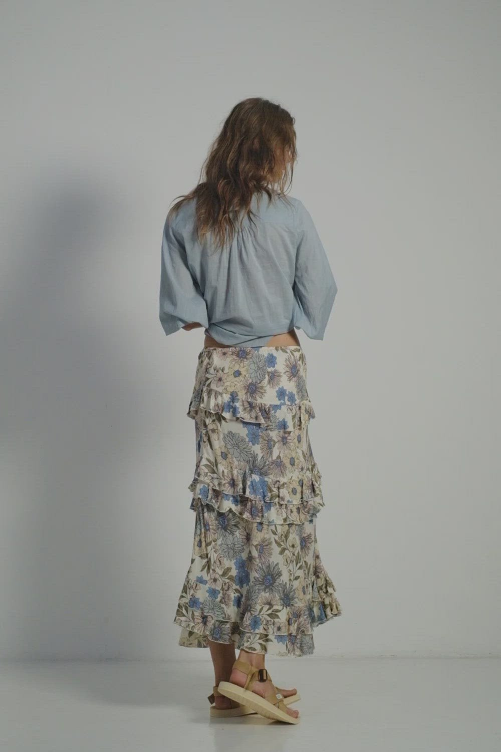 A woman wearing floral skirt and a blue blouse by Lilya