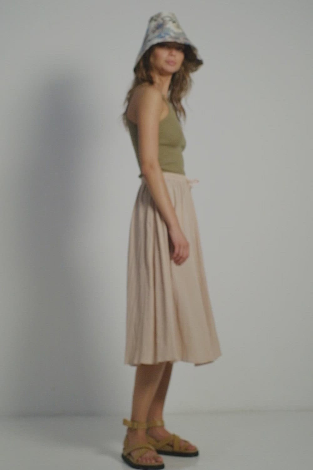 A woman in a bucket floral hat, khaki top and midi skirt by Lilya