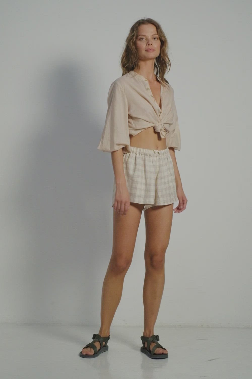 A woman wearing summer linen shorts in check print and a beige blouse by Lilya