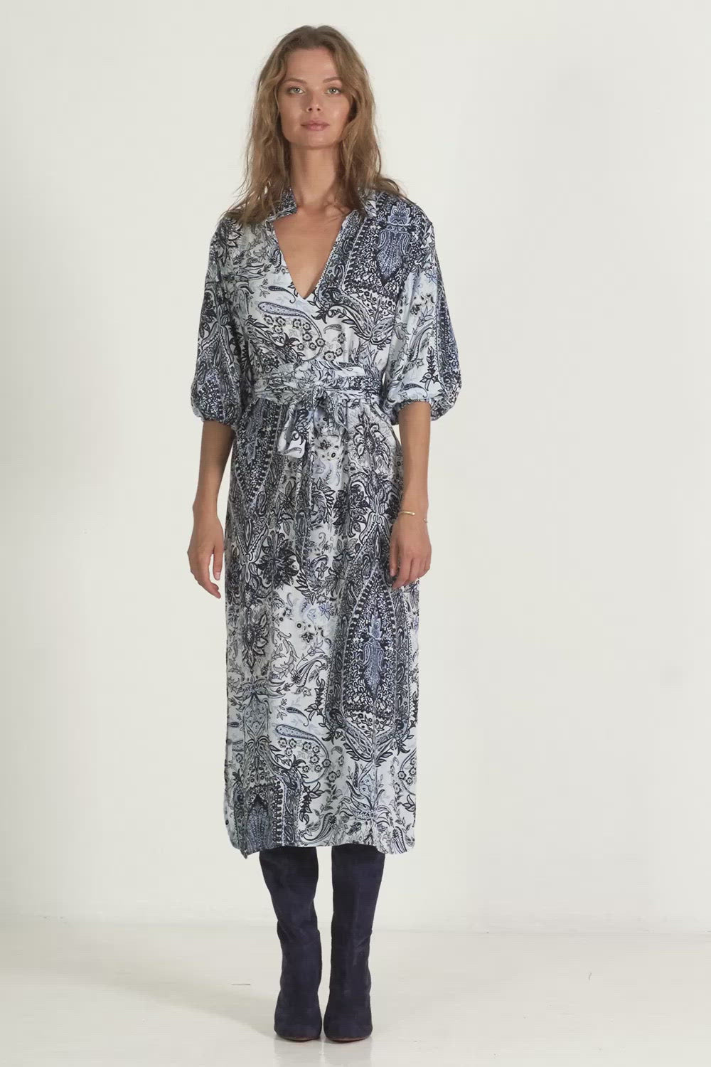 A woman wearing a Calma paisley maxi dress by Lilya for winter