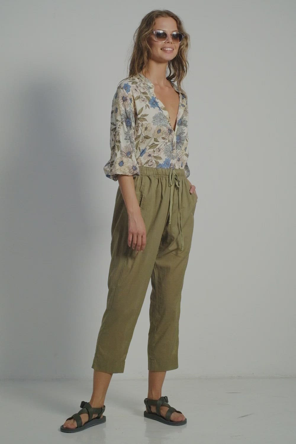 A woman wearing summer look by Lilya: khaki cotton pants and casual floral blouse