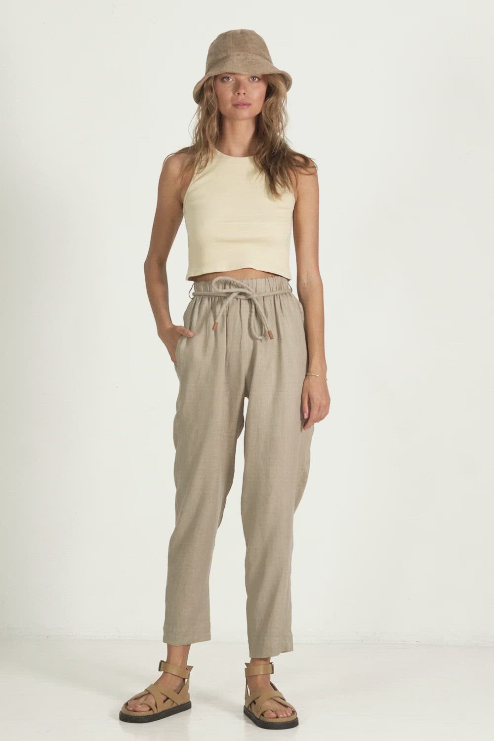 A woman in plain high waisted linen pants for summer by Lilya
