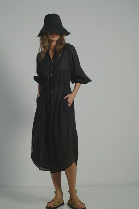 A woman wearing a classic Lilya black summer dress