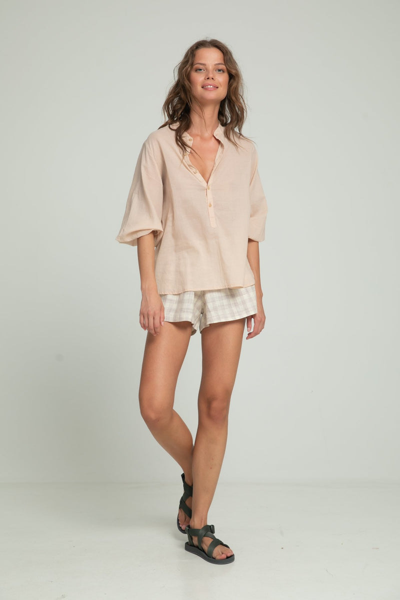 A woman wearing a light beige blouse and check summer shorts by Lilya
