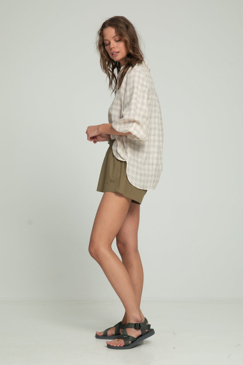 A woman in a linen check long sleeve blouse and khaki summer shorts by Lilya