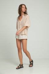 A woman in a nude blouse and check cotton shorts by Lilya