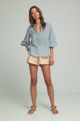 A woman wearing a cotton blue blouse and cotton shorts by Lilya