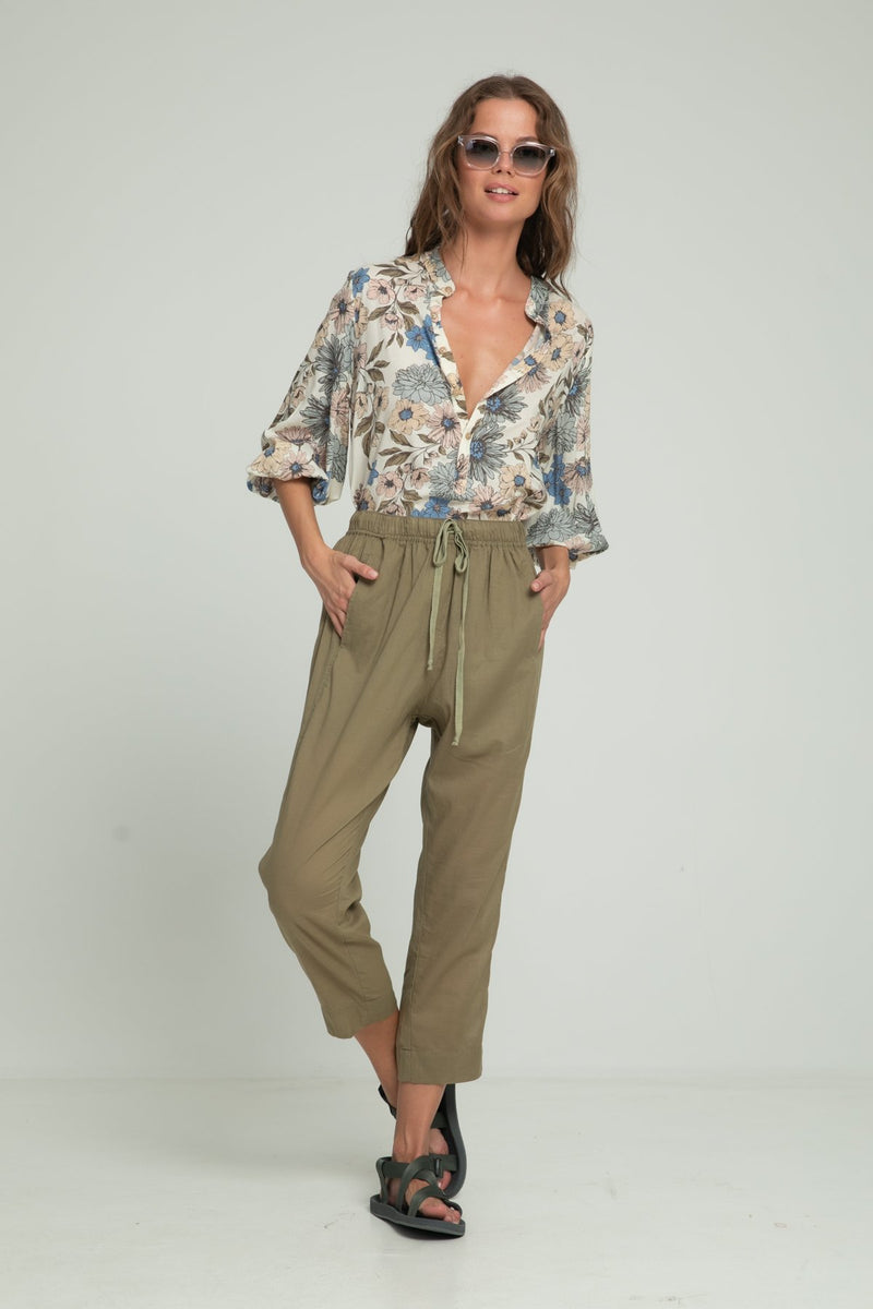 A woman wearing floral blouse and khaki pants by Lilya