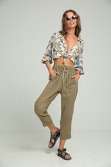 A woman wearing a summer look of floral blouse and khaki pants by Lilya