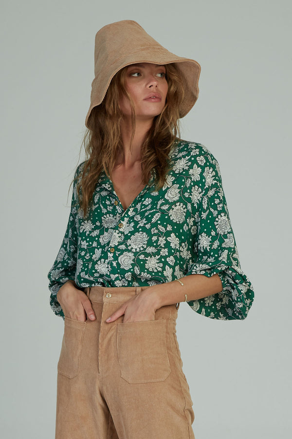 A woman in a long sleeve floral Agatha blouse by Lilya in Australia