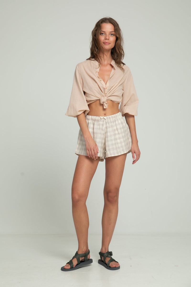 A woman in a sandalwood casual blouse with buttons and check cotton shorts by Lilya