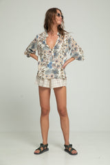 A woman wearing long sleeve floral blouse and shorts by Lilya