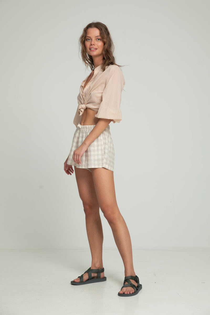 A woman wearing light beige blouse for summer and cotton check casual shorts by Lilya