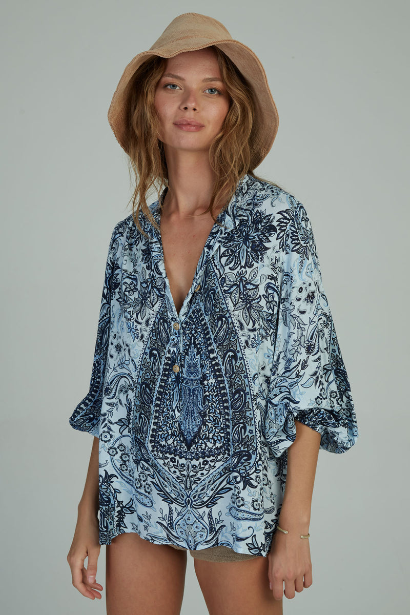 A woman in a blue paisley winter top by Lilya