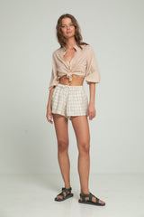 A woman in a sandalwood casual long sleeve blouse and check cotton shorts by Lilya