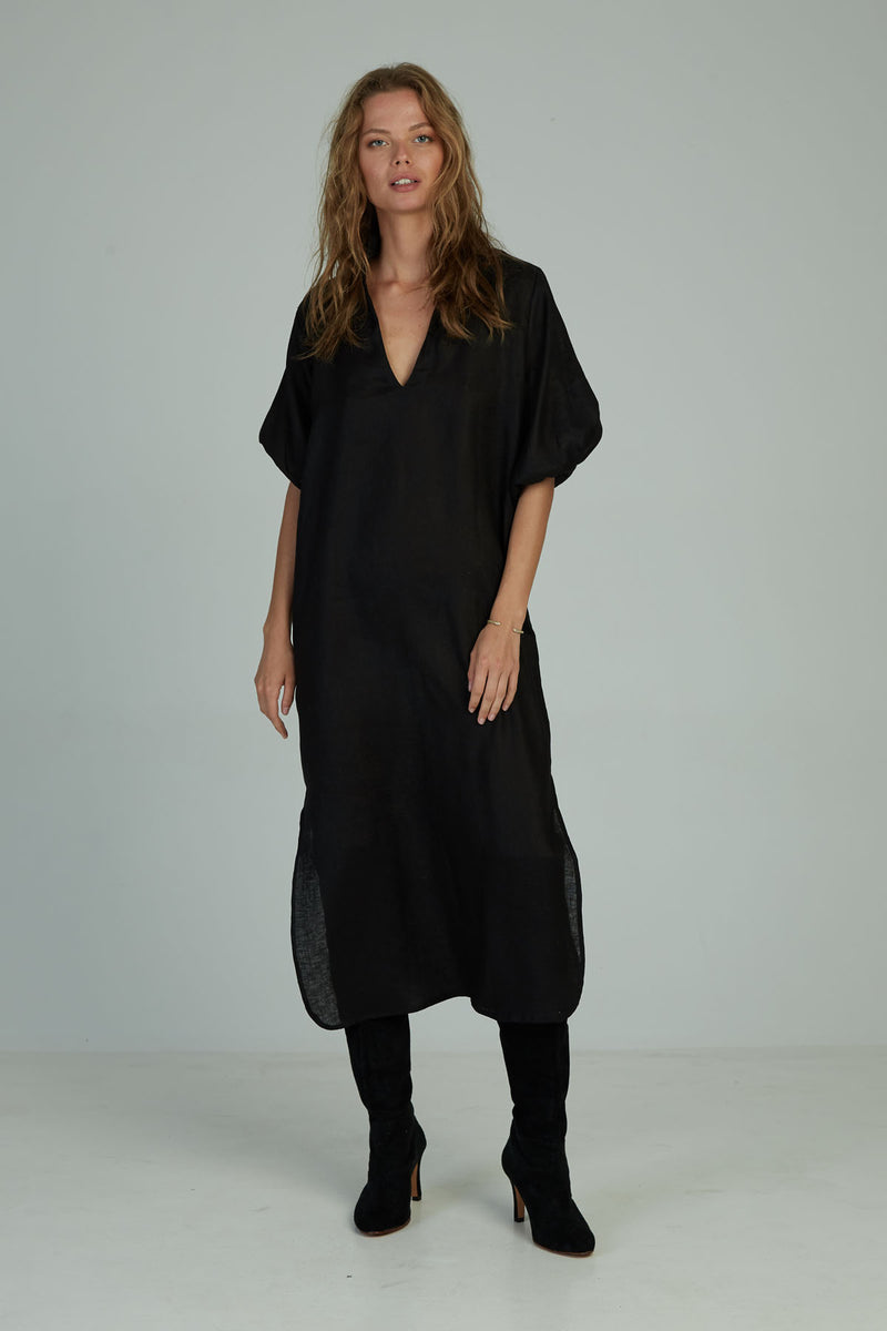 A woman in a black kaftan style linen maxi dress for winter by Lilya