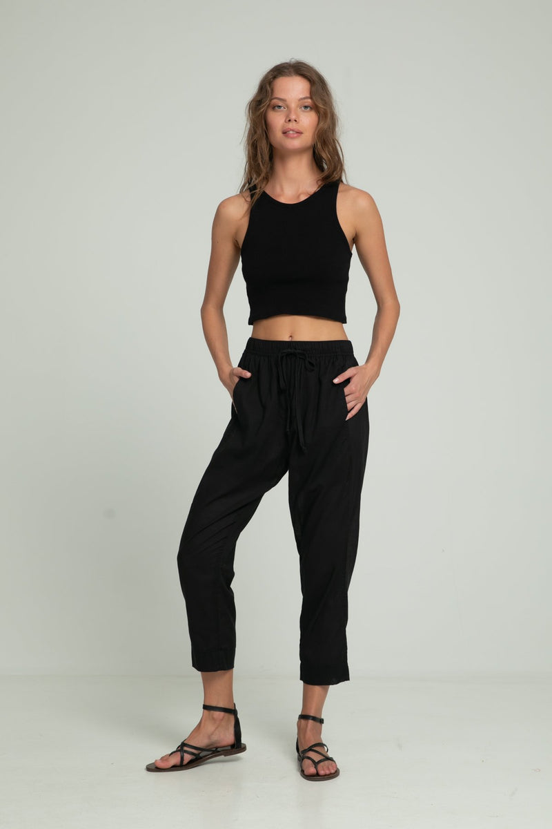 A woman wearing cotton black pants and a black crop top by Lilya