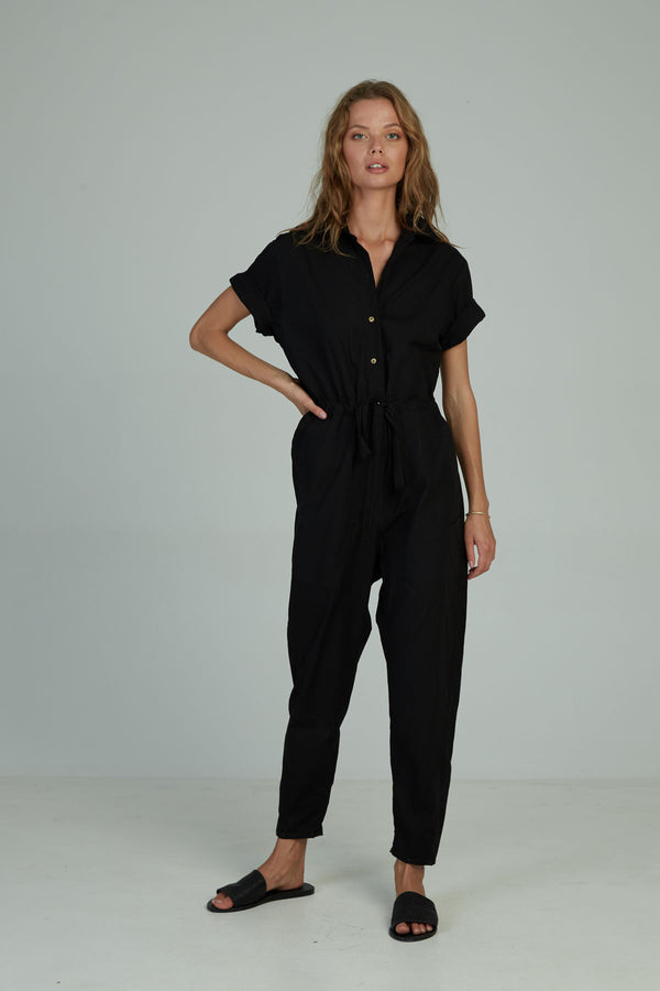 A woman in a black cotton jumpsuit by Lilya