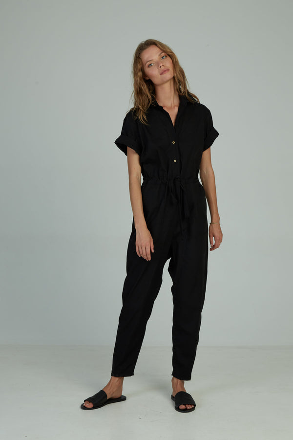 A woman in a black utilitarian jumpsuit by Lilya in Australia