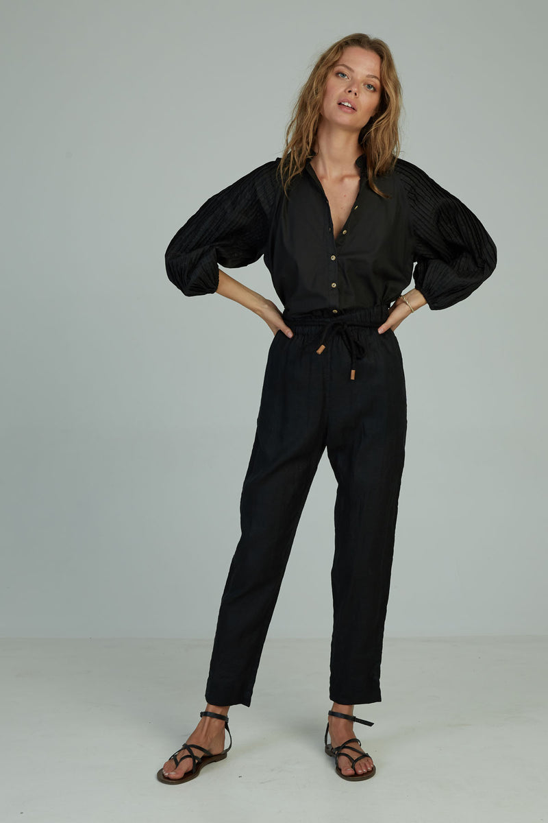 A woman wearing black classic high waisted linen pants by Lilya