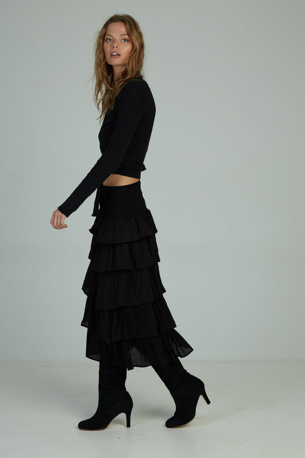 A woman in an elastic ruched black maxi skirt by Lilya in Australia