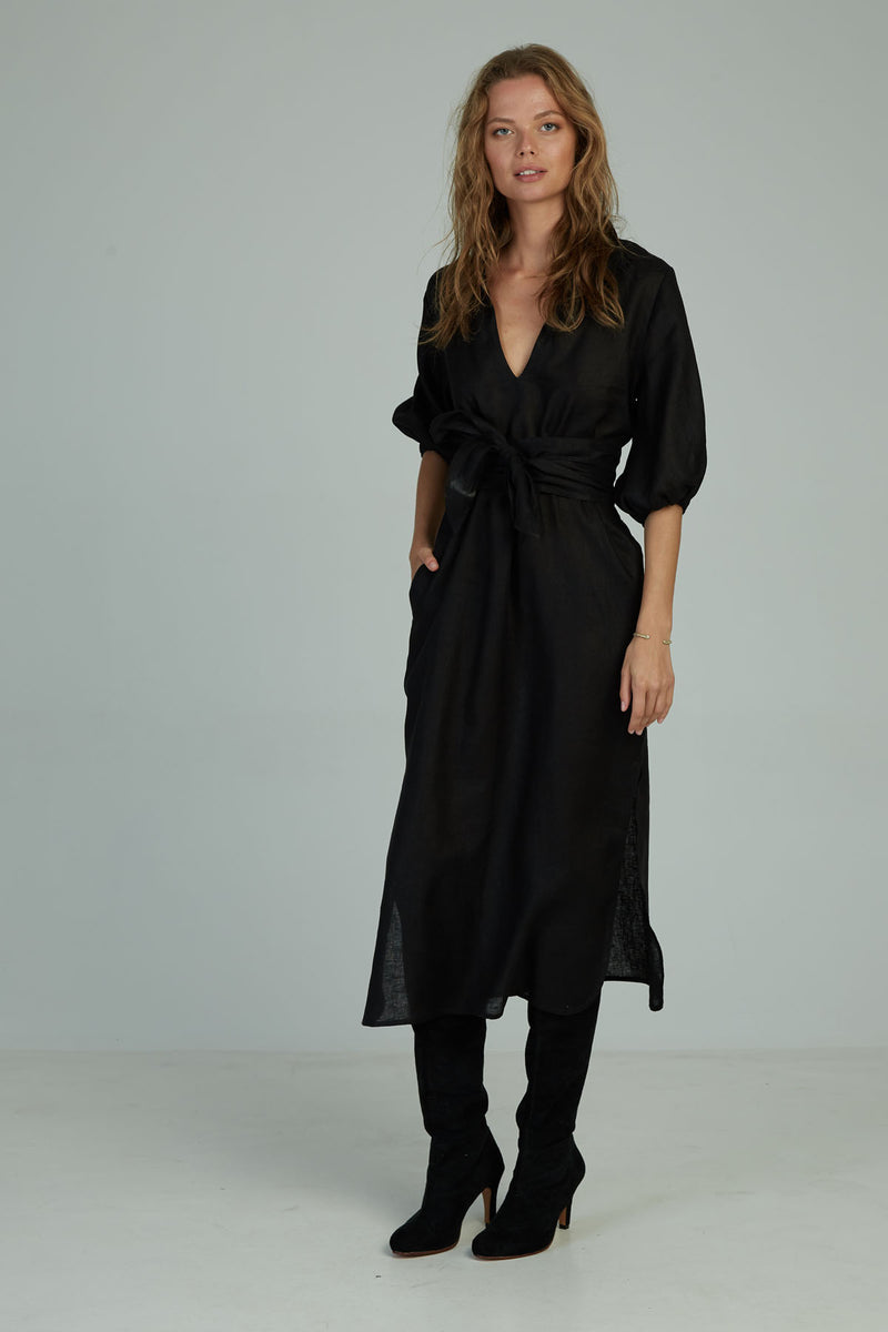 A woman in a black linen maxi dress with matching belt by Lilya