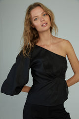 A woman wearing a dressy black linen one shoulder top by Lilya