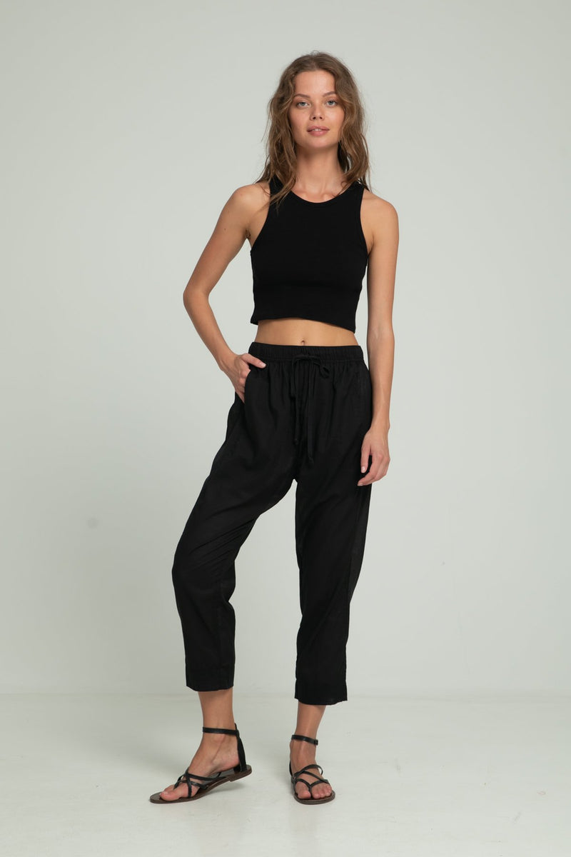 A woman wearing black cotton pants and a black crop top by Lilya