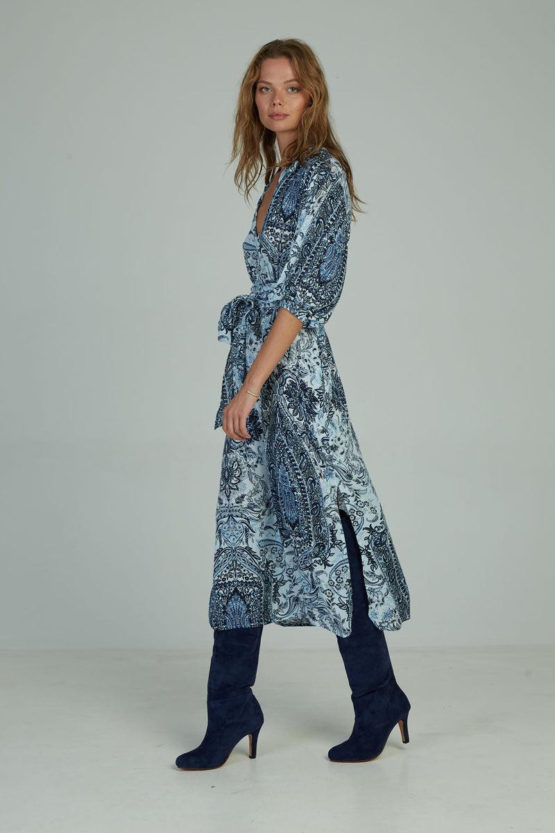 A woman in a blue paisley kaftan maxi dress by Lilya