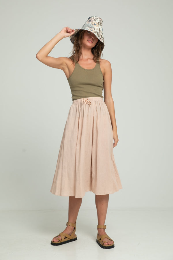 A woman wearing summer look by Lilya: floral bucket hat, khaki singlet and a skirt