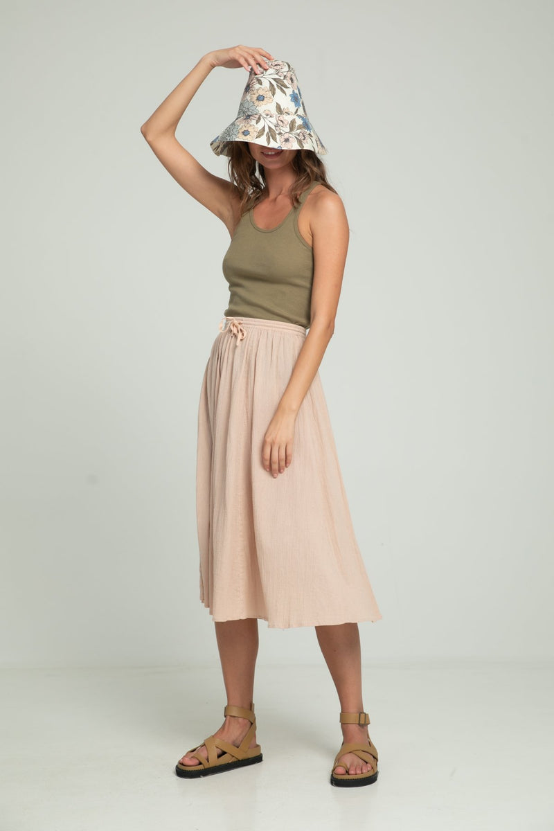 A woman in a floral bucket hat, khaki top and skirt by Lilya