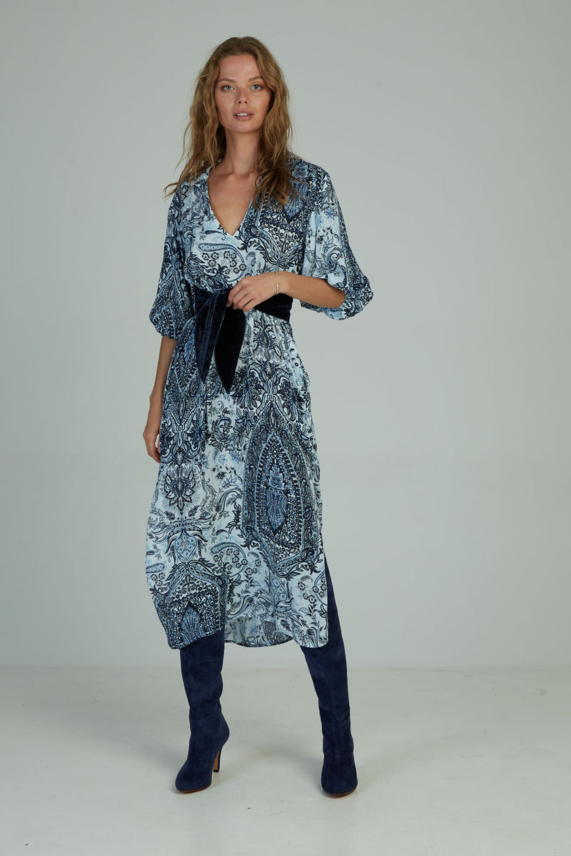 A woman wearing a paisley maxi dress by Lilya