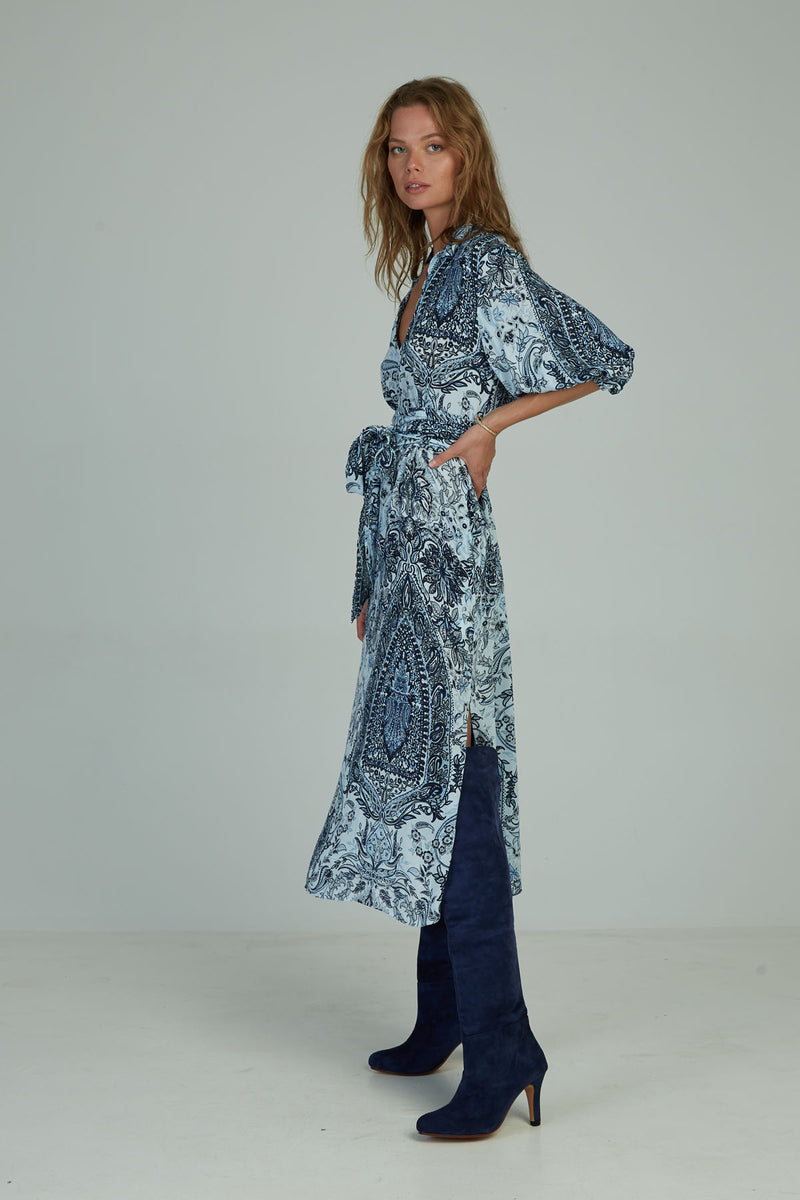 A woman wearing a winter paisley maxi dress by Lilya