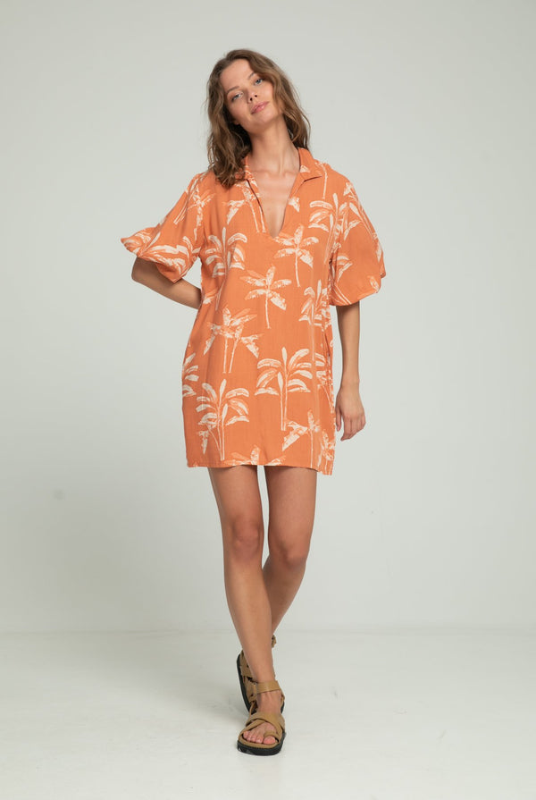 A woman in a resort dress with banana leaf print for summer by Lilya