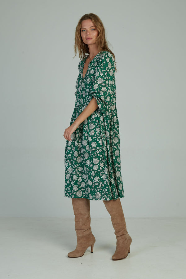 A woman in a long sleeve floral midi dress by Lilya