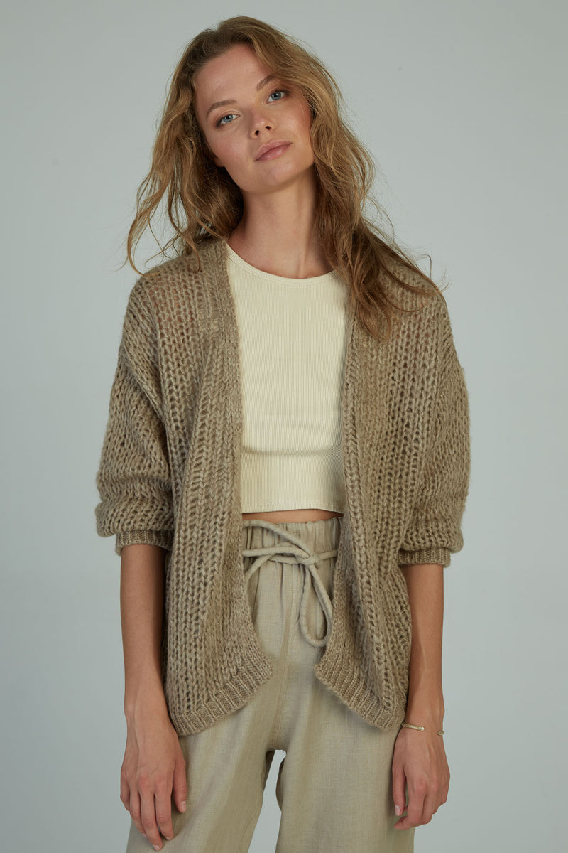 A woman wearing a casual knit cardigan by Lilya in Australia