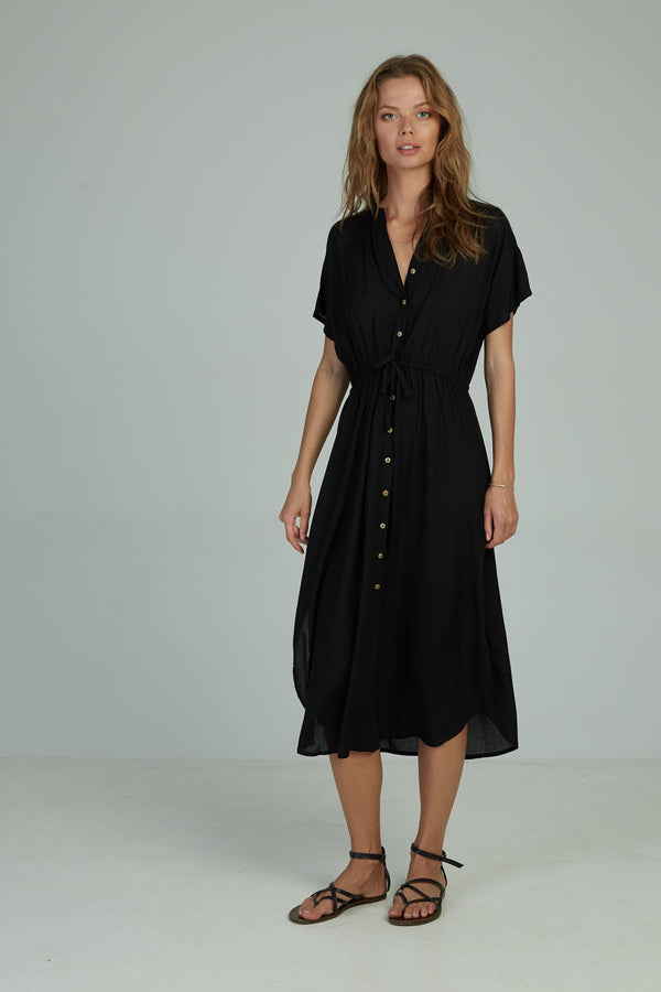A woman in a black midi shirt dress by Lilya