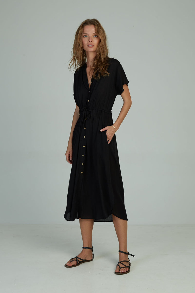 A woman in a black shirt dress by Lilya in Australia