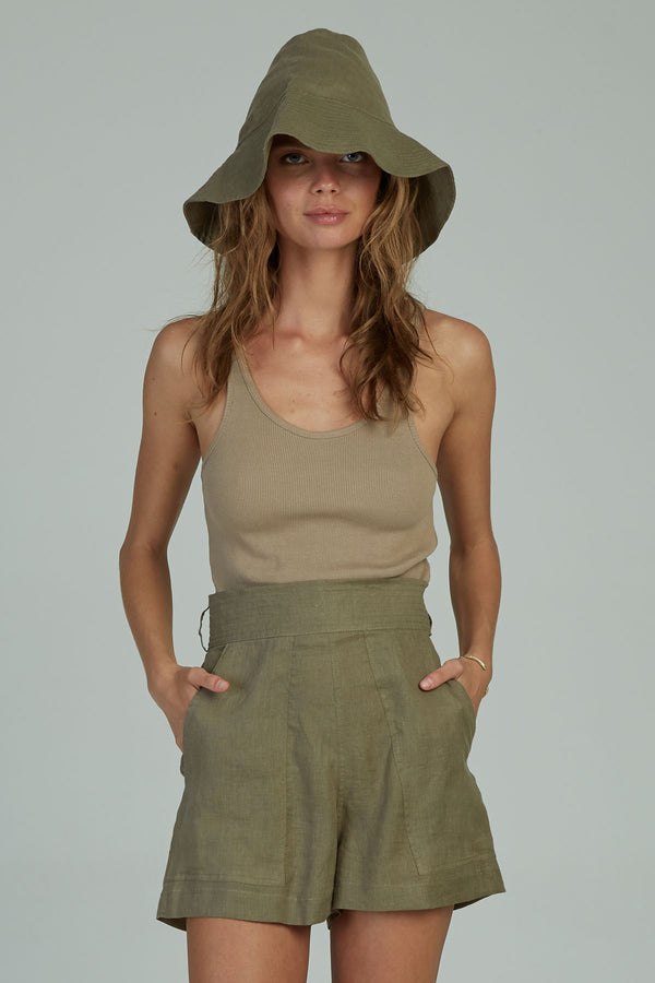 A woman wearing high wasited linen shorts by Lilya
