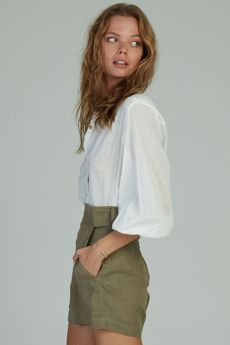 A woman in a casual white linen top by Lilya