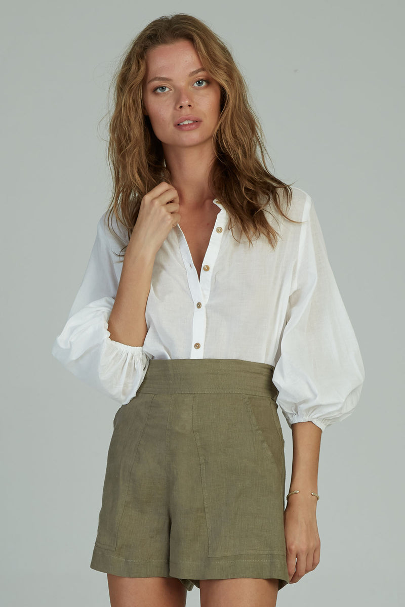 A woman in a white button down cotton top by Lilya