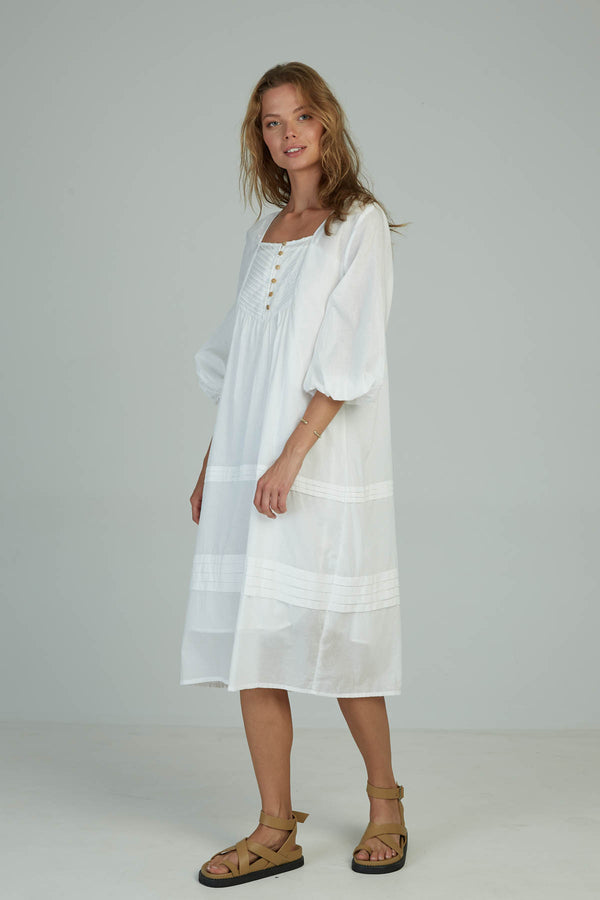 A woman in a white cotton summer dress made by Lilya in Australia