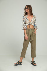 A woman in khaki cotton summer pants and floral blouse by Lilya