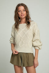 A woman wearing khaki shorts from cotton and ivory sweater by Lilya