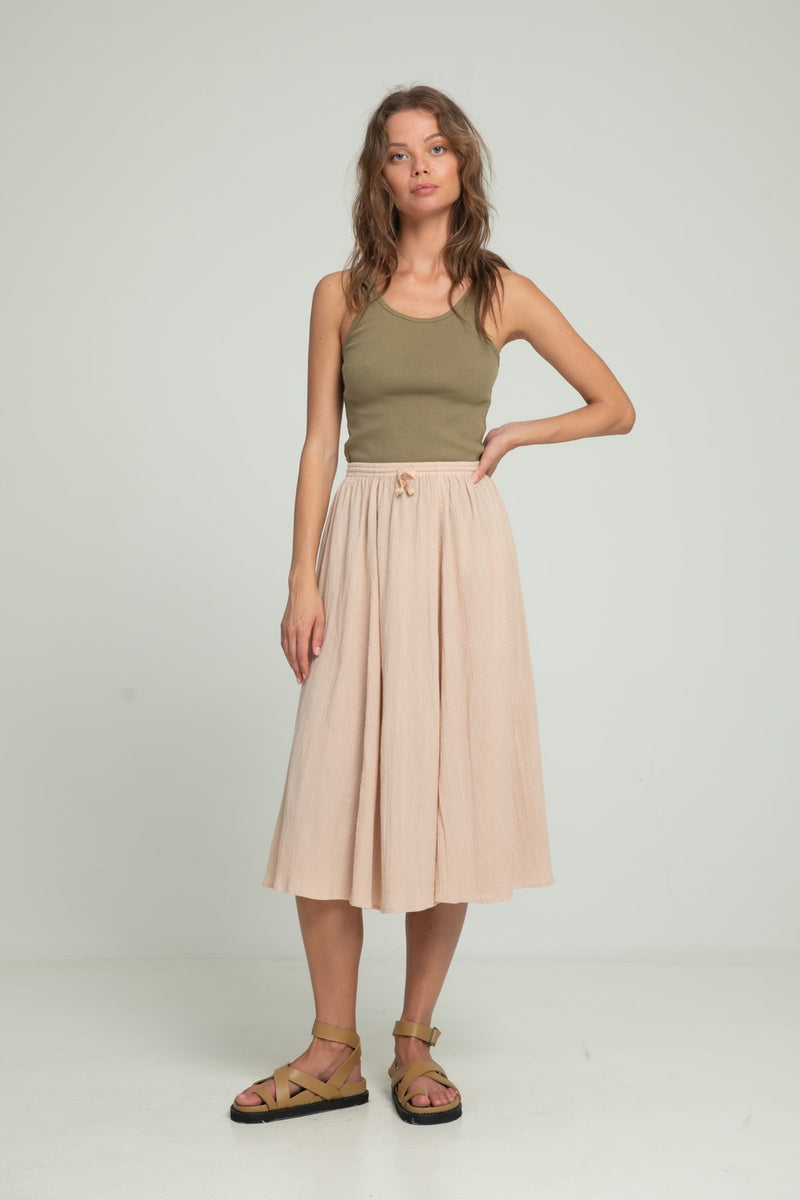 A woman wearing a ribbed cotton khaki singlet and a pink sand skirt by Lilya